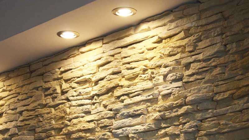 Come illuminare una parete in pietra dentro e fuori casa for Salone con parete in pietra